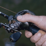 right hand holding a rod and baitcaster