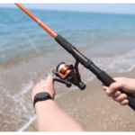 Man Spins Line on Reel of Fishing Rod at Sea