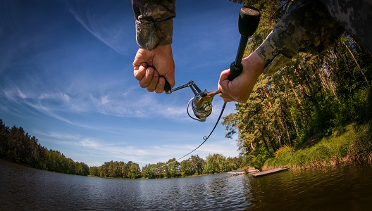 Fisherman with spinning reel on the lake