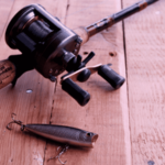 baitcast reel, rod and lure on plank