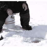 ice angler sitting on bucket with ice rod and reel