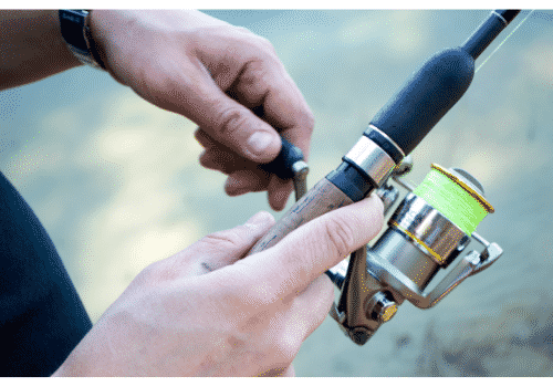 hand holding a fishing rod and spinning reel