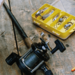fishing reel and bait on plank