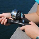 fisher holding spincast rod and reel