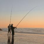 2 anglers surf fishing at dawn