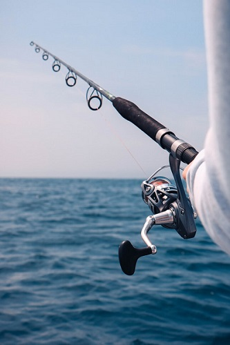 spinning rod and reel against blue water