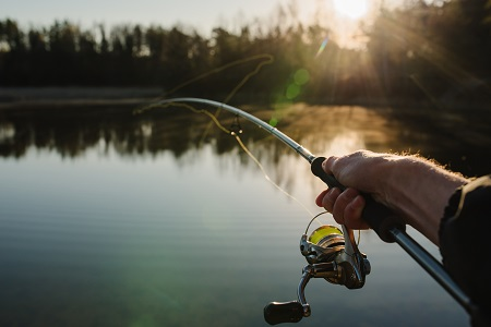fisherman with rod, spinning reel on the river bank