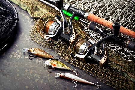 fishing rods and spinning reels with accessories on table